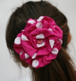 Ruffled flower worn as hairclip